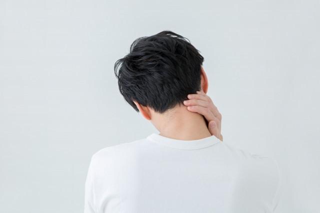 首こりのため、首のこりを触る男性写真